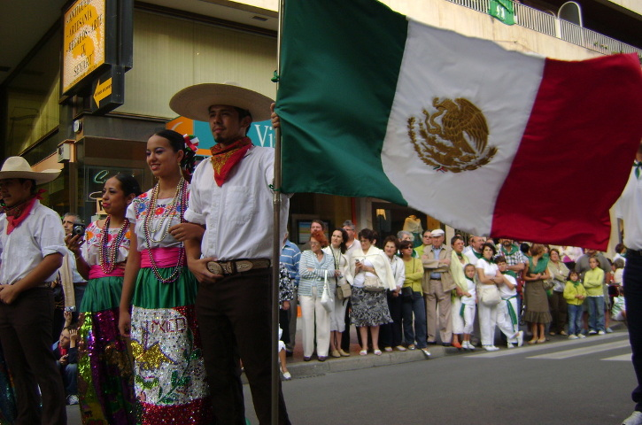 Two dancers posing with the flag of Mexico