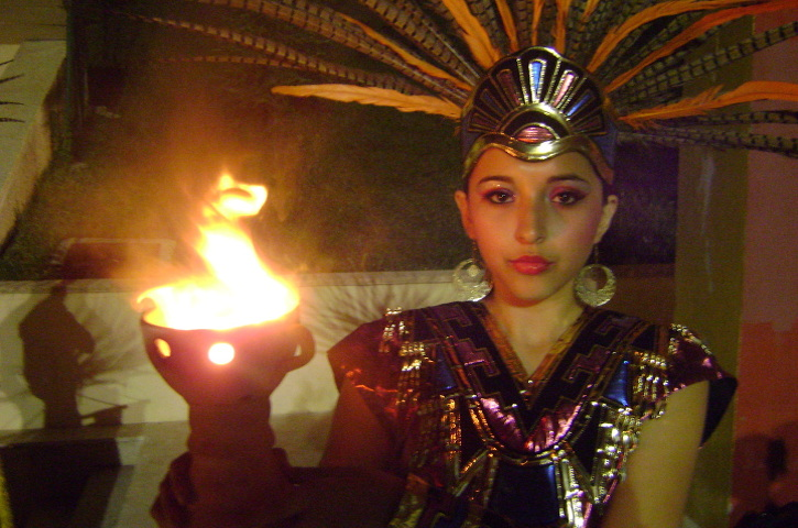 Woman in Aztek headdress holding traditional flame
