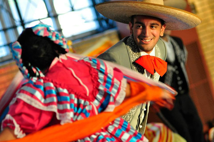 Dancer smiling mid-dance in traditional charro suit