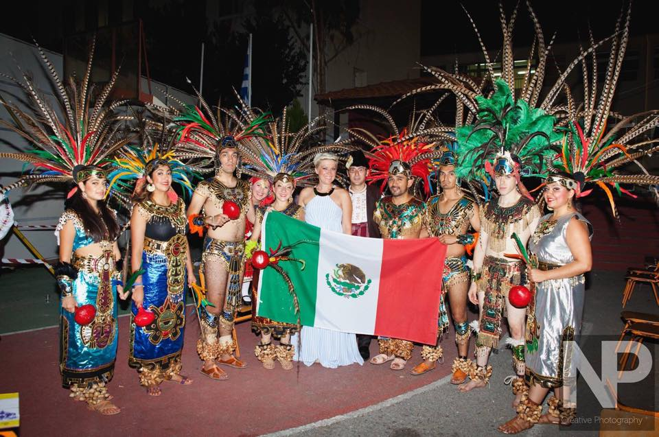 Group of dancers posing with flag of Mexico